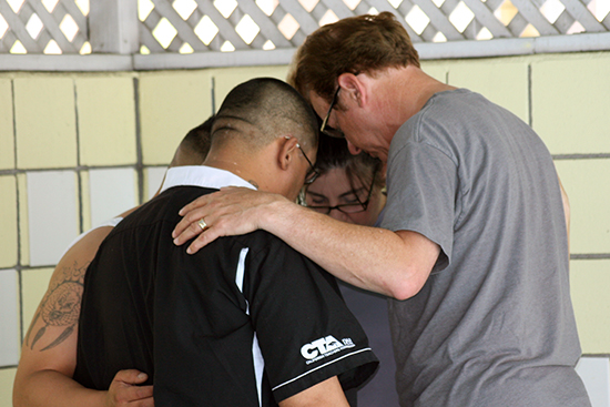 Pastor Ron prays with a family before they are baptized at Motel Church